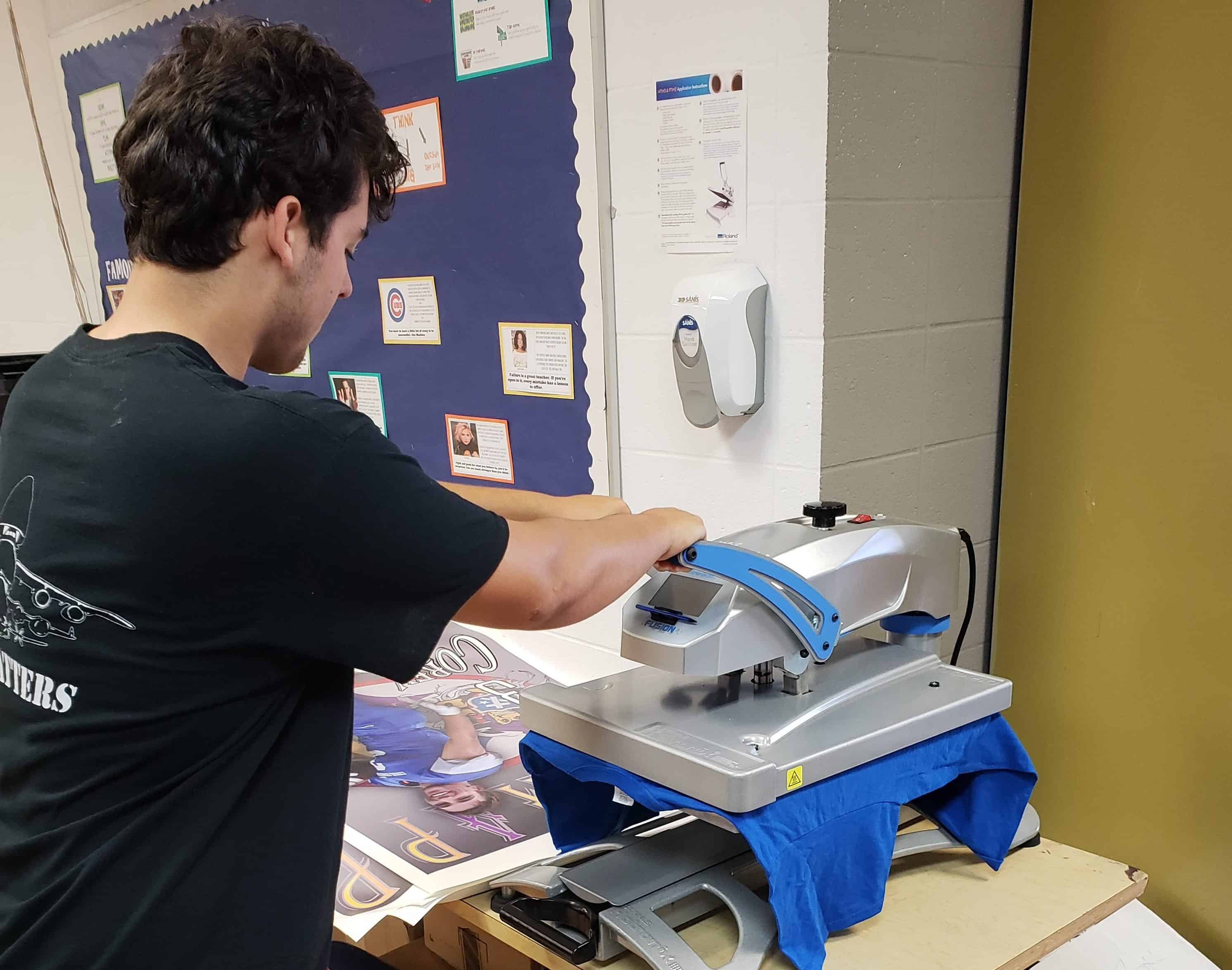 A Hoopeston Student uses a heat press to create apparel